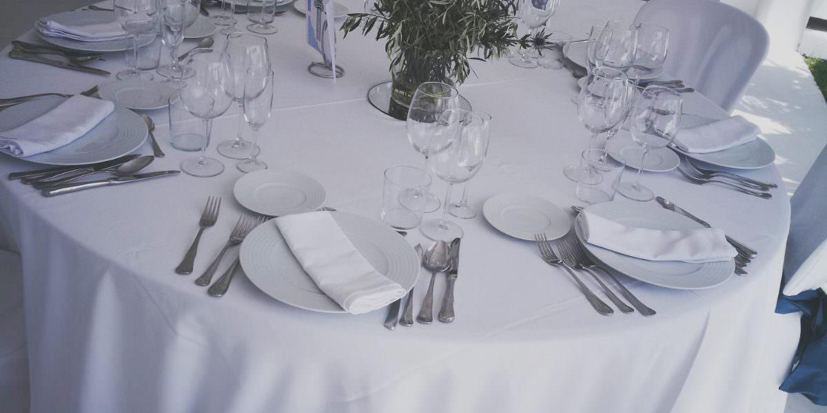 Mesa circular con platos y cubiertos en el salón cerrado